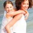 Mother giving daughter piggyback ride on beach — Stock Photo #10313955