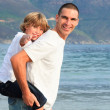 Father giving his son piggyback ride on beach — Stock Photo #10313956