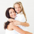 Beautiful mother and her daughter looking at the camera on the bed — Stock Photo