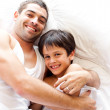 Charming father and his son looking at the camera on the bed — Stock Photo #10313965