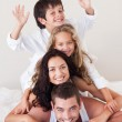 Royalty-Free Stock Photo: Joyful family having fun together on the bed