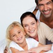 Parents and daughter on bed smiling at the camera — Stock Photo