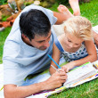 Stock Photo: Dad and daughter painting in a garden