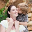 Portrait of a son kissing his mother in a park — Stock Photo