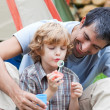 Father and son having fun with bubbles — Stock Photo