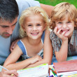 Stock Photo: Smiling children drawing with their father