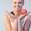 Blonde woman showing chocolate and apple focus on chocolate and apple — Stock Photo