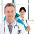 Attractive confident doctor in a line — Stock Photo