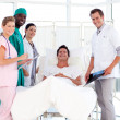 Doctors attending to a patient smiling at the camera — Stock Photo #10314644