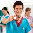 Friendly doctor with his team in the background — Stock Photo
