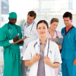 Beautiful doctor with her team in the background — Stock Photo #10314698