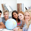 Smiling teenagers in a library working with a terrestrial globe — Stock Photo #10315553