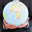 Close-up of a charismatic businessman holding a globe — Stock Photo