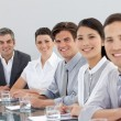 Foto Stock: Smiling multi-ethnic business in meeting