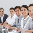 Photo: Smiling multi-ethnic business in meeting