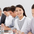 Smiling business partners taking notes in a meeting — Stock Photo #10316374