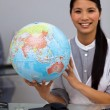 Assertive businesswoman holding terrestrial globe — Stock Photo
