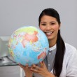 Confident asian businesswoman holding terrestrial globe — Stock Photo