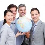 Portrait of a multi-ethnic businessteam holding a globe — Stock Photo