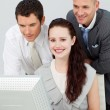 Smiling businesswoman and two businessmen using a computer — Stock Photo #10316782