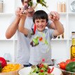 Portrait of a happy father preparing a salad with his son - Stock Photo
