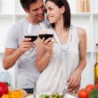 Smiling lovers drinking wine and preparing a salad — Stock Photo #10316997