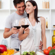 Smiling couple drinking wine and preparing a salad — Stock Photo #10316998