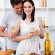 Portrait of a smiling couple cooking and toasting with wine — Stock Photo #10317005