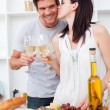 Woman kissing her boyfriend and toasting with white wine — Stock Photo