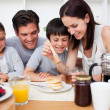 Happy family having breakfast together — Stock Photo