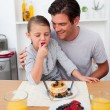 Little girl eating strawberries with her father — Stock Photo #10317028