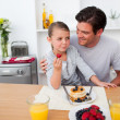 Stock Photo: Smiling father and his daughter eating fruits