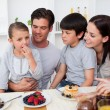 Smiling family eating pancakes for breakfast — Stock Photo