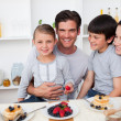Stock Photo: Young family eating fruits and pancakes for breakfast