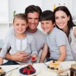 Stock Photo: Portrait of parents and children havinf breakfast together