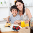 Smiling little boy having breakfast with his mother — Stock Photo