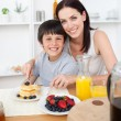 Stock Photo: Smiling little boy having breakfast with his mother