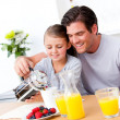 Cheerful father and his daughter having breakfast together - Stock Photo