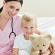 Smiling little boy holding a teddy bear on a hospital bed — Stock Photo
