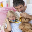Stock Photo: Daughter and father playing doctors with a teddy bear