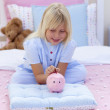 Little girl saving money in a piggy bank — Stock Photo #10317291