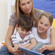 Mother reading a book with her daughter and son — Stock Photo