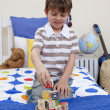 Little boy playing with alphabet cubes in his bedroom — Foto de Stock