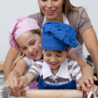 Stock Photo: Mother and children baking cookies in the kitchen