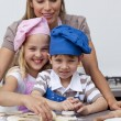 Mother helping her children baking — Stock Photo