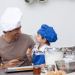 Smiling father and son eating home-made cookies — Stock Photo
