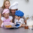 Happy family baking cookies in the kitchen — Stock Photo #10317358