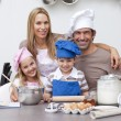 Smiling parents helping children baking in kitchen — Stockfoto #10317380
