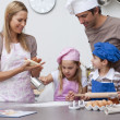 Mother and father helping children baking in the kitchen — Stock Photo