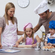 Stock Photo: Parents helping children baking in the kitchen